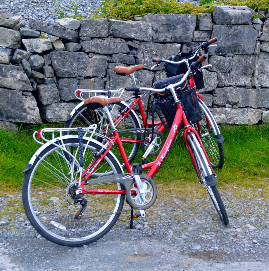 Zwei rote Damenfahrräder abgestellt vor einer alten Steinmauer