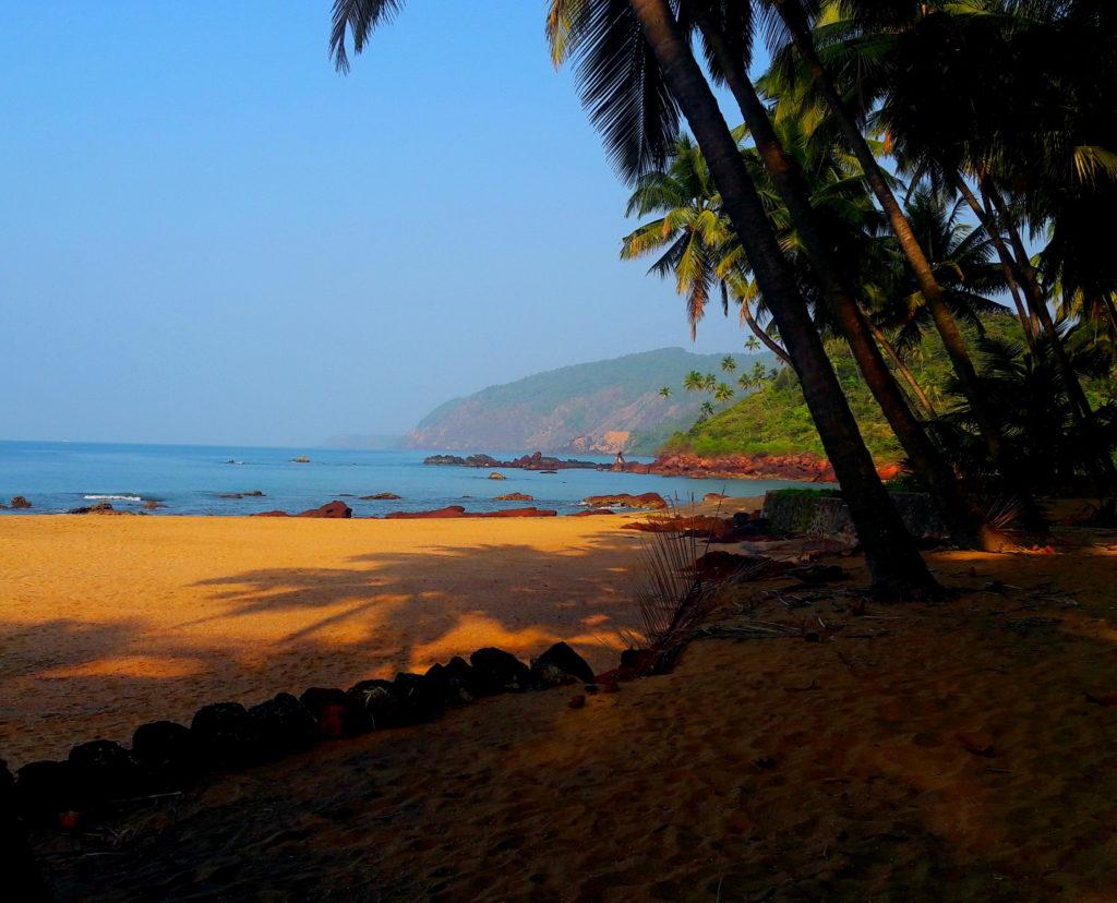Eine menschenleere Bucht am Kola-Beach in Goa, gesäumt von Palmen mit grünen Palmenhügeln im Hintergrund